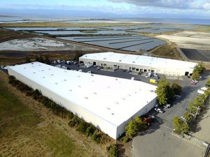 drone shot of white Astec Acrylic Roof Coating on two industrial buildings surrounded by trees green grass in foreground salt water flats of San Francisco bay in background with cloudy blue sky