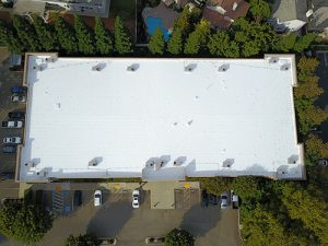 drone shot of white Astec Acrylic coated roof on Stockton office building surrounded by trees and parked cars