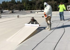 three men wearing protective gear one man rolls out roofing membrane on white acrylic roof on Ross department store