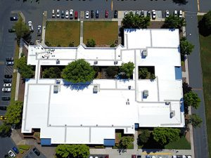 drone shot of PVC roof on the Employment Development Department surrounded by trees and parking lot