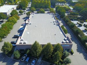 drone shot of grey GE Silicone roof on stockton office building surrounded by trees, cars and parking lots