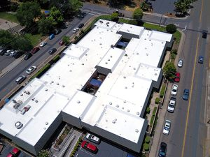 drone shot of large white TPO roof on assisted living building surrounded by cars on streets