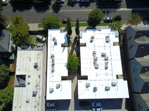 drone shot of two bright white silicone roofs on sacramento apartment building with air conditioning units surrounded by trees and homes on right