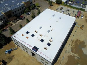 drone shot of TPO single ply roof on new commercial building in Pleasanton surrounded by fresh dirt and construction vehicles