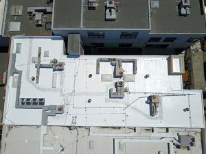 drone shot of silicone roof with air conditioning units on Berkeley school surrounded by other roofs