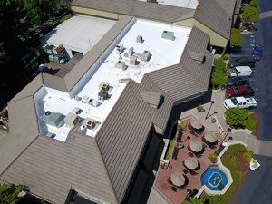 drone shot of TPO and tile roof air conditioning units umbrella covered eating area and parking lot on right