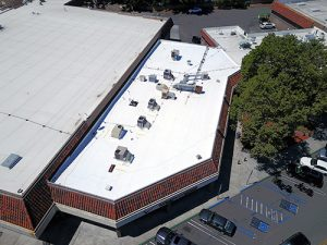drone shot of white TPO roof with eight air conditioning units on jewelry retail store large tree to right cars and parking lot lower left