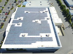 drone shot of white Astec Acrylic roof coating on large roof covered with solar panels parking lot on right and left side of building