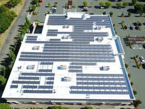 drone shot of solar paneled roof covered and white Astec Acrylic Coating on Kohl's in Santa Rosa surrounded by grey parking lot and green trees