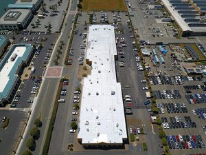 drone shot of long white GE Silicone covered roof of commercial office building in Richmond Marina surrounded by parking lots streets and some buildings