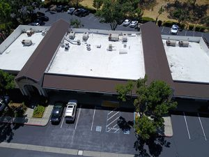 drone shot of two composition shingled roofs in middle of three white roofs on Subway Sandwiches building in Martinez cars and parking lot in front and back