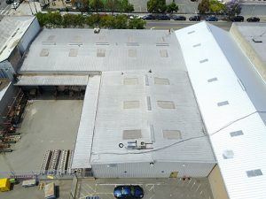 drone shot of sheet metal roof on comcast building with white coated metal roof on right parking lot with car lower left