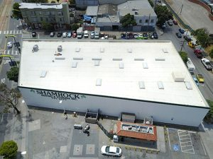 drone shot of white GE silicone roof over TPO on Shamrock's commercial roof surrounded by parking lot cars and buildings empty parking lot small red building in lower half of photo
