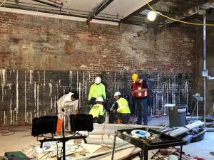 half red half black brick wall with water seepage five men mixing waterproofing compound in basement surrounded by lights and construction equipment