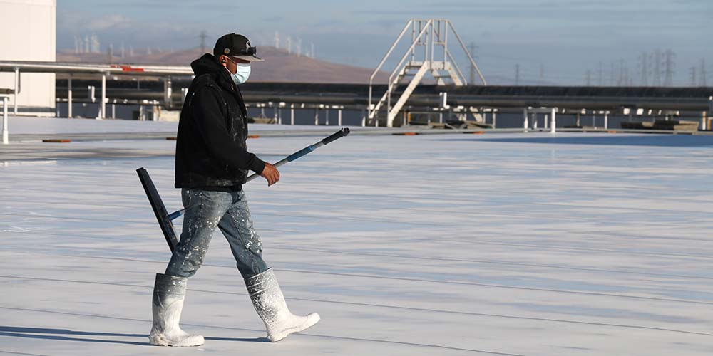 Single man walks across roof wearing covid mask, white boots, carrying a stick.