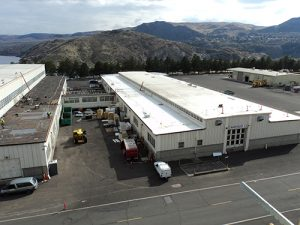 drone shot of PVC roof on two warehouses at Grand Coulee Dam construction equipment rolling hills in background with cloudy sky