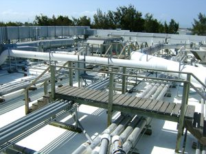roof covered in pipes and air conditioning. white Acrylic coating barely visible through pipes and walkway Dupont industrial roof trees and blue sky in background