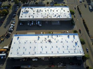drone shot of roofing crew installing white TPO covered roofs dotted with air vents on two light industrial buildings surround by streets and parking lots