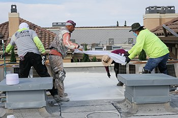 Four roofers putting down a polyester fabric mesh and acrylic coating.