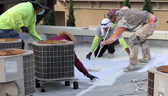 Four Men doing roof restoration on cypress apartment complex in san jose