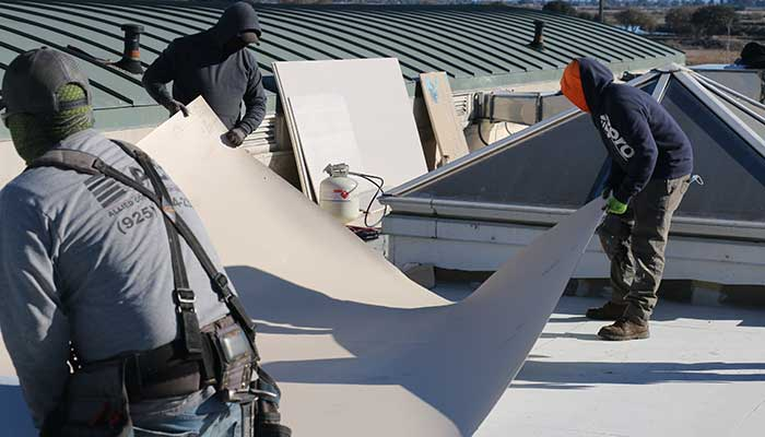 Three foofers position large sheet of roofing material.