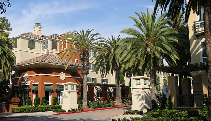 Spanish tiled apartment complex at the Cypress Apartments in San Jose with palm trees in foreground