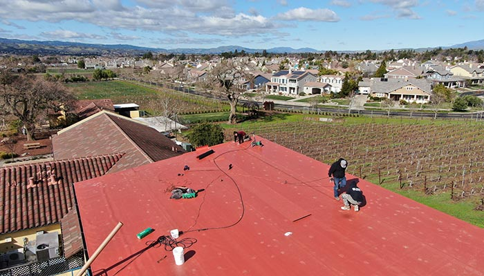 Red TPO roof over winery with vineyard and subdivision in background.
