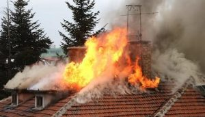 Bright orange flames and smoke as fire consumes a tile roof from underneath